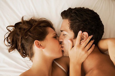 Close-up of young couple in bed kissing.